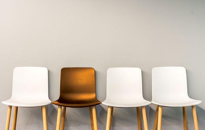 An image of three white and one bronze armless chairs with a grey backdrop.