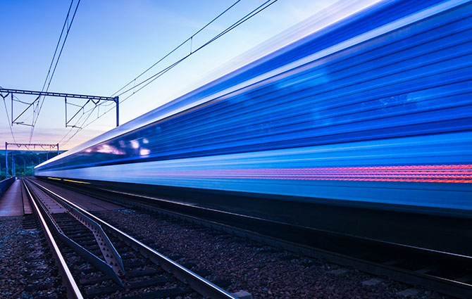 An image of a blue train driving passed on railway tracks.