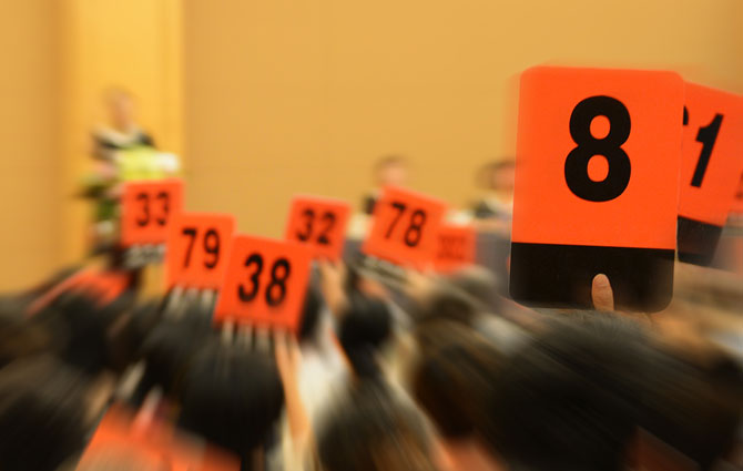 Multiple orange number cards at an auction.